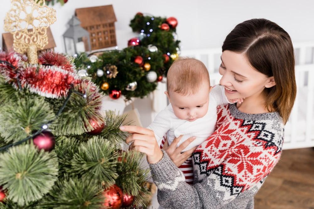 Mor og baby der pynter årets juletræ