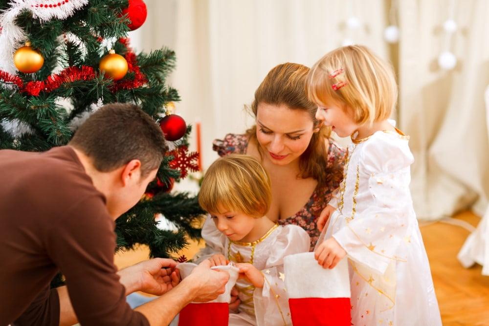 Julehygge med forældre og 2 børn ved juletræet